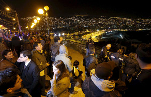 People stand and watch the ocean on Cerro Baron hill, in Valparaiso city September 16, 2015, after a mass evacuation of the entire coastline during a tsunami alert after a magnitude 8.3 earthquake hit off the coast of Chile on Wednesday.
